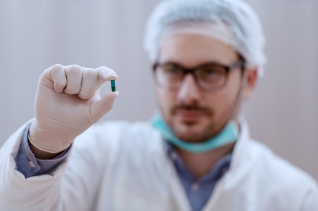 Lekarz trzymając kapsułkę. selektywne skupienie na dłoni.