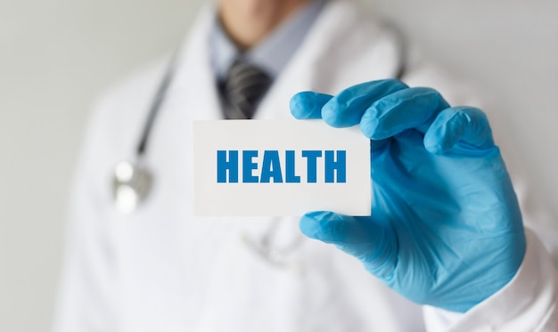 Lekarz trzymając kartę z tekstem zdrowie, pojęcie medyczne