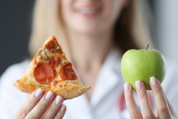 Lekarz trzymając kawałek pizzy i zielone jabłko w jego ręce zbliżenie. właściwa koncepcja odżywiania