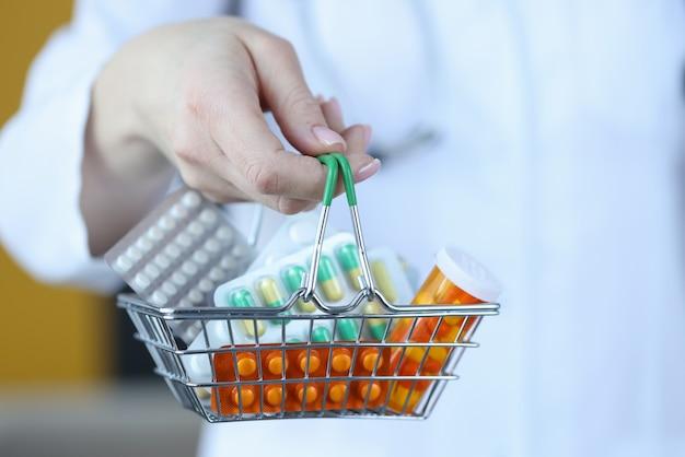Lekarz trzymając mały koszyk z lekami zbliżenie. farmaceutyczna koncepcja biznesowa