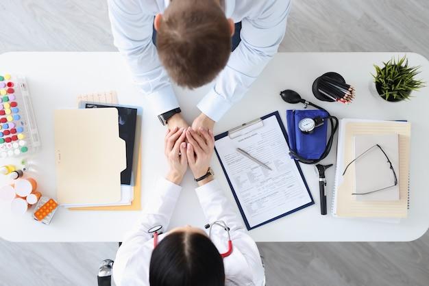 Lekarz, trzymając pacjentów za ręce w widoku z góry kliniki