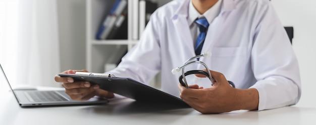 Lekarz trzymając plik raportu pacjenta, aby ocenić objawy na biurku.