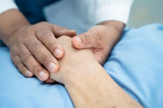 Lekarz trzymając rękę asian pacjent starszy kobieta z miłością.