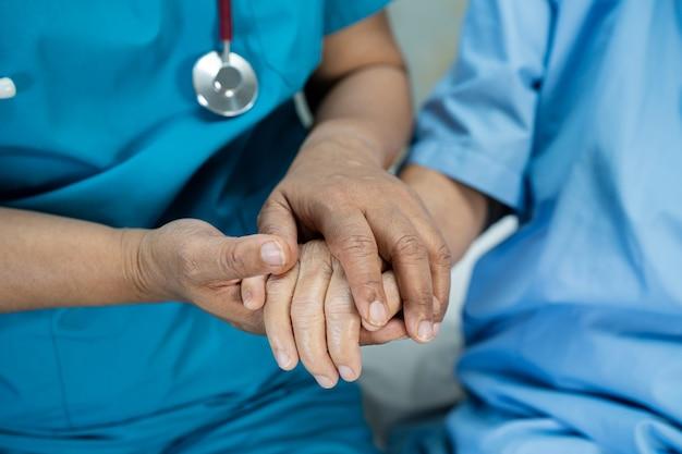 Lekarz trzymając się za ręce azjatycki starszy kobieta pacjent z miłością