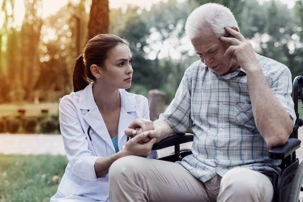 Lekarz trzymając starą rękę mężczyzny na wózku inwalidzkim