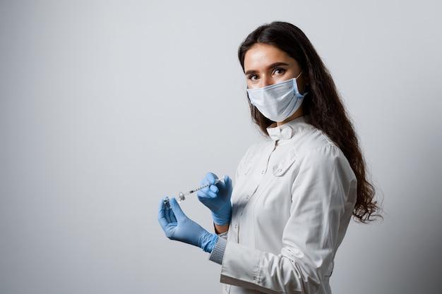 Lekarz trzymając strzykawkę ze szczepionką na koronawirusa. szczepienie covid-19. zatrzymaj kwarantannę. atrakcyjna dziewczyna w rękawiczkach medycznych z strzykawką i lekiem