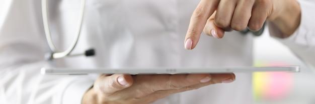 Lekarz trzymając tablet w dłoniach i wskazując na to palcem zbliżenie. koncepcja zdalnego poradnictwa pacjenta
