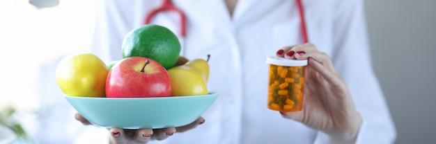 Lekarz trzymając talerz owoców i słoik medycyny zbliżenie biorąc koncepcję witamin