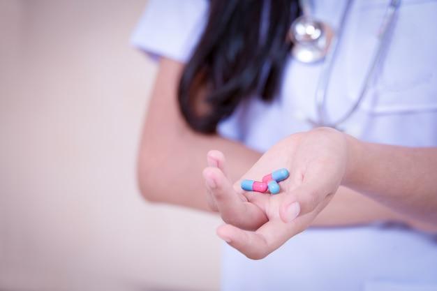 Lekarz trzymający lek w kapsułkach na białym tle