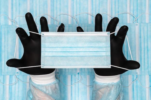 Lekarz trzymający niebieską chirurgiczną maskę medyczną w dwóch czarnych rękawicach ochronnych w koncepcji rąk