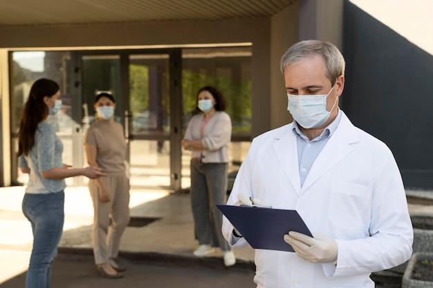 Lekarz trzymający notatnik w centrum szczepień z pacjentami na zewnątrz