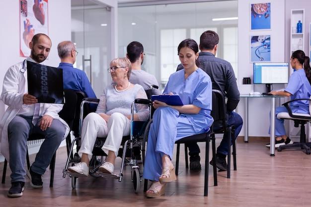 Lekarz trzymający rentgen pacjenta wyjaśniający diagnozę pielęgniarce i niepełnosprawnej kobiecie