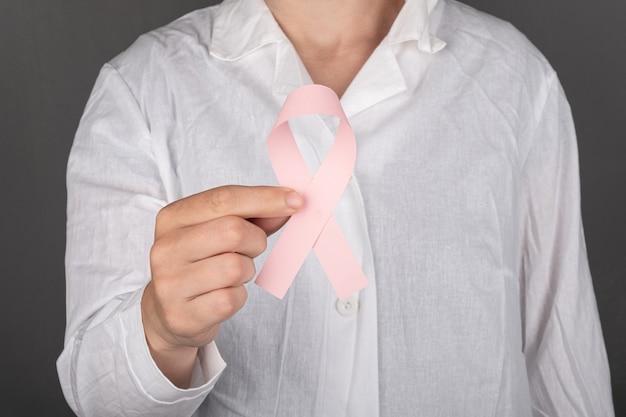 Lekarz trzymający różową wstążkę symbol walki z rakiem piersi.