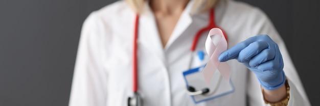 Lekarz trzymający różową wstążkę w ręku w gumowej rękawiczce zbliżenie koncepcja dzień raka piersi