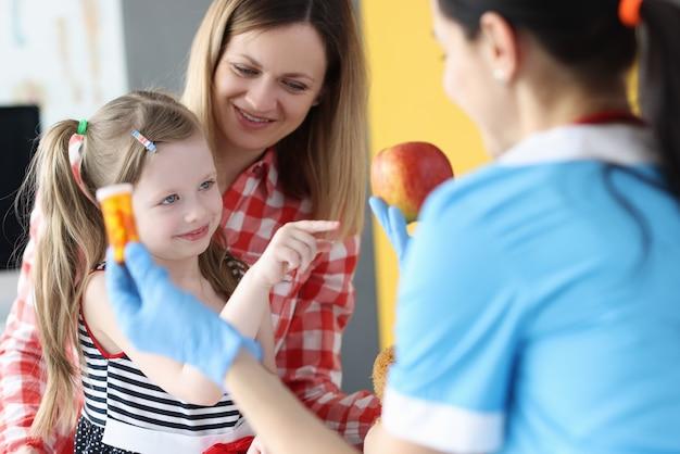 Lekarz trzymający słoik leków i jabłka przed małą dziewczynką i matką