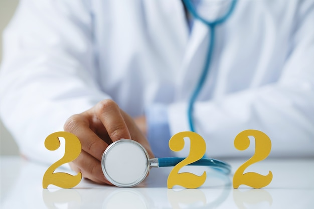 Lekarz trzymający stetoskop w pobliżu złotego drewnianego numeru 2022 pomysł na nowy trend w leczeniu medycznym