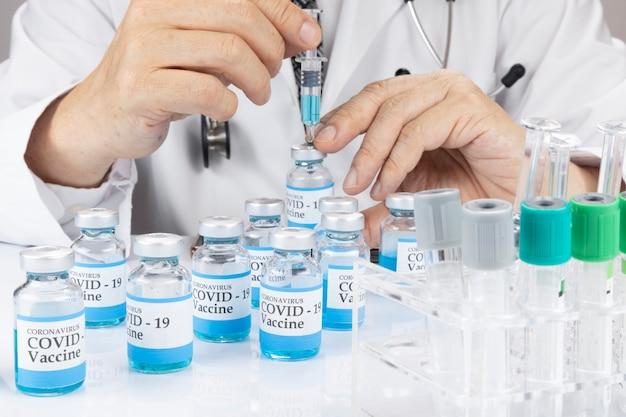 Lekarz trzymający strzykawkę z fiolką z płynną szczepionką koncepcja szczepienia covid19