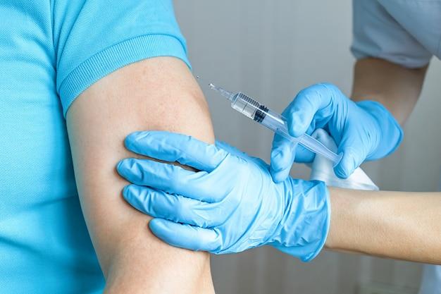 Lekarz trzymający strzykawkę ze szczepionką przeciwko koronawirusowi covid-19, robi szczepienie, zastrzyk. lek na sars-cov-2, covid, wirus, opieka zdrowotna, testy, koncepcja leczenia.
