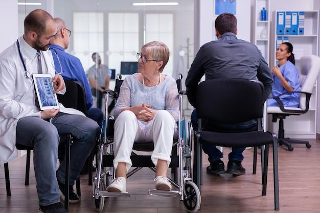 Lekarz trzymający tablet pc z prześwietleniem, wyjaśniający diagnozę niepełnosprawnej starszej kobiecie na wózku inwalidzkim