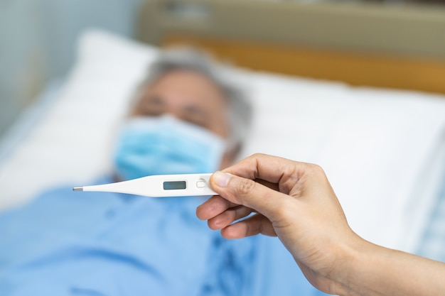 Lekarz trzymający termometr cyfrowy do pomiaru azjatyckich starszych lub starszych pacjentów starszej kobiety w masce na twarz ma gorączkę w szpitalu, zdrowa, silna koncepcja medyczna.