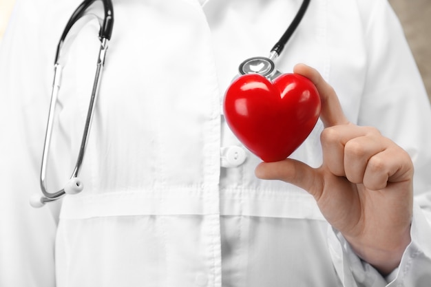 Lekarz trzymający w ręku plastikowe serce, zbliżenie