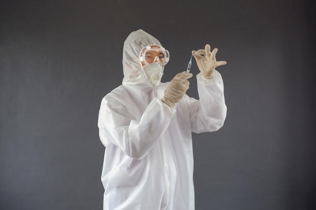 Lekarz ubrany w kombinezon i maskę na twarz ze strzykawką gotową do wstrzyknięcia szczepionki pacjentowi