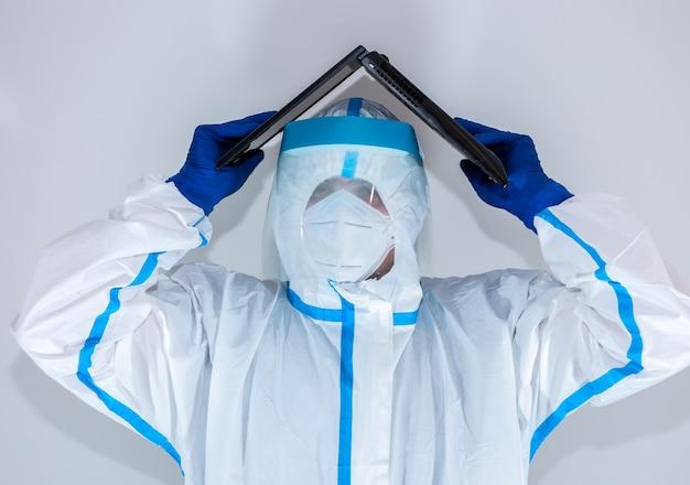Lekarz ubrany w medyczny kombinezon ochronny, gogle, maskę i rękawiczki pracuje na laptopie. ochrona przed epidemią wirusa. koronawirus (covid-19). pojęcie opieki zdrowotnej.