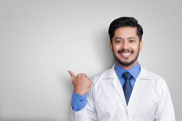 Lekarz ubrany w mundur, uśmiechający się podczas prezentacji i wskazujący na białym tle z miejsca na kopię
