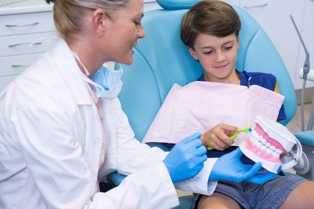 Lekarz uczy chłopca szczotkowania zębów
