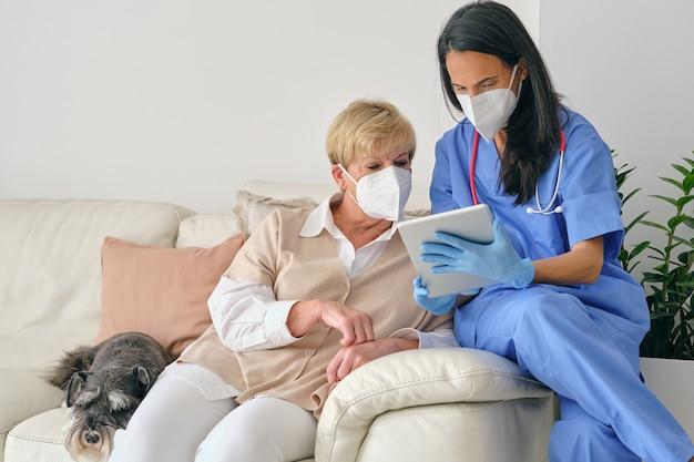 Lekarz udostępnia tablet starszemu pacjentowi podczas badania w domu