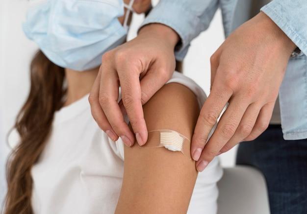 Lekarz umieszcza bandaż na ramieniu małej dziewczynki z bliska