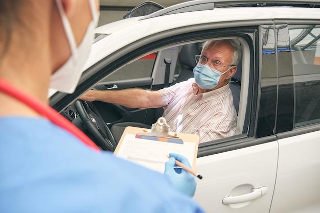 Lekarz upraw rozmawiający z męskim kierowcą w samochodzie