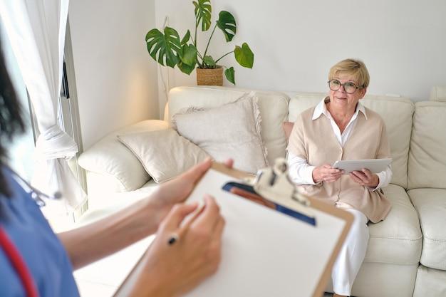 Lekarz upraw wchodzący w interakcję ze starszym pacjentem na kanapie