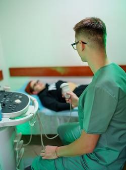 Lekarz usg wykonuje usg jamy brzusznej chłopca. chłopiec jest badany przez ultrasonografa.