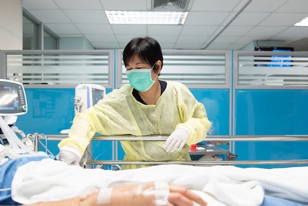 Lekarz używa monitora z objawami życiowymi do opieki medycznej nad wirusem grypy, koronawirusem, cre. lub vre. zakażony starszy pacjent na łóżku pacjenta na oddziale intensywnej terapii (oiom).
