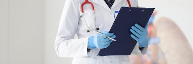 Lekarz w białym fartuchu i rękawiczkach posiada długopis i schowek