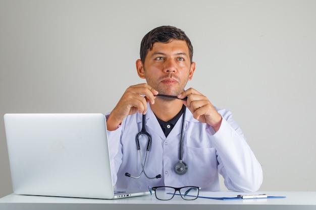 Lekarz w białym fartuchu, myślący stetoskopem, wpatrujący się w bok i kontemplujący