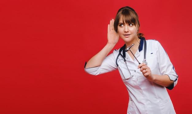 Lekarz w białym fartuchu na czerwonym tle trzyma młotek neurologiczny i czegoś słucha
