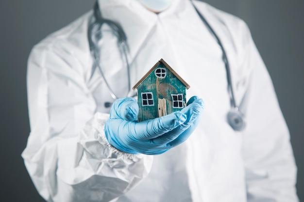 Lekarz w białym fartuchu ochronnym chroni mały domek na szarym tle