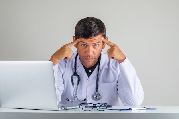 Lekarz w białym fartuchu, stetoskop dotyka skroni palcami i wygląda na zmęczonego