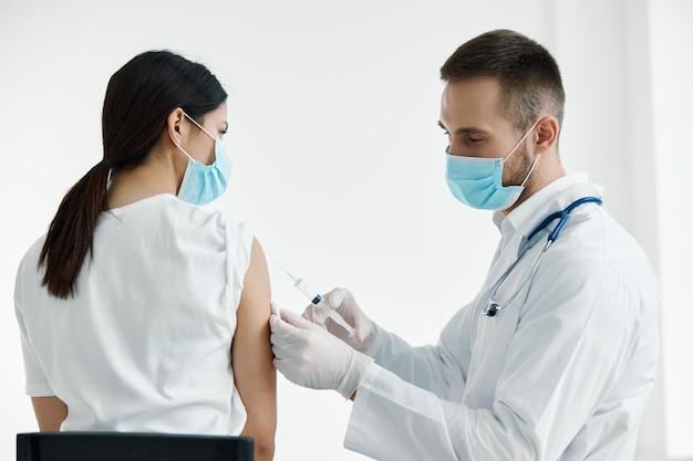 Lekarz w białym fartuchu wstrzykuje womans rękawice ochronne na ramię szczepienia