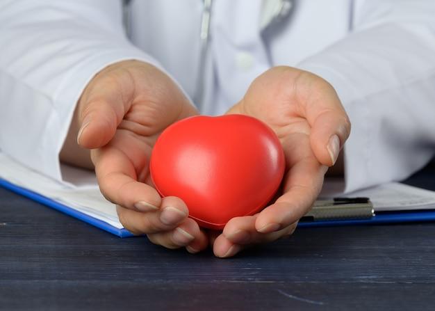 Lekarz w białym fartuchu z czerwonym sercem