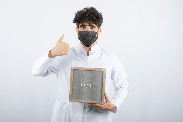 Lekarz w białym fartuchu ze stetoskopem pokazując kciuk na białym tle.