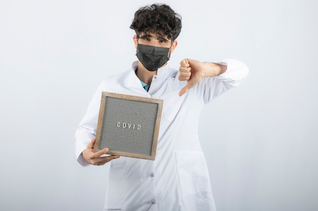Lekarz w białym fartuchu ze stetoskopem pokazując kciuk w dół na białym tle.