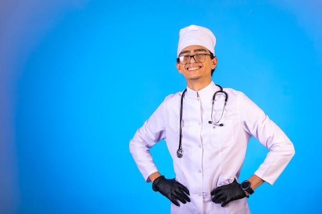 Lekarz w białym mundurze medycznym ze stetoskopem położył ręce na pasie i uśmiechnął się