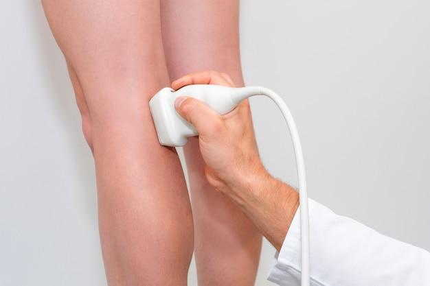 Lekarz w białym mundurze ze sprzętem diagnostycznym wykonuje badanie ultrasonograficzne za pomocą urządzenia na nogach pacjentki. mężczyzna chirurg, flebolog pracujący w nowoczesnej klinice. narzędzia medyczne w szpitalu.
