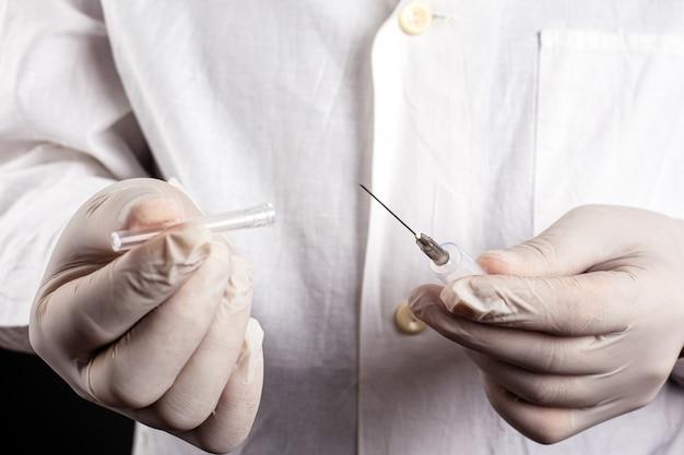 Lekarz w białym płaszczu i rękawiczkach otwiera zbliżenie strzykawki. szczepienie leczenie iniekcyjne przeziębienie przeciwko odrze covid-19.