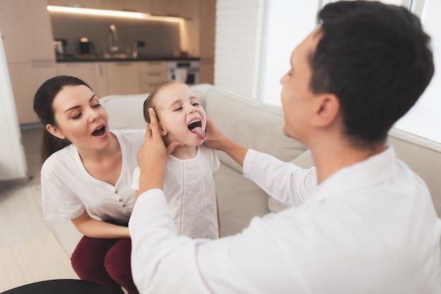 Lekarz w białym płaszczu sprawdza gardło chorej dziewczyny.