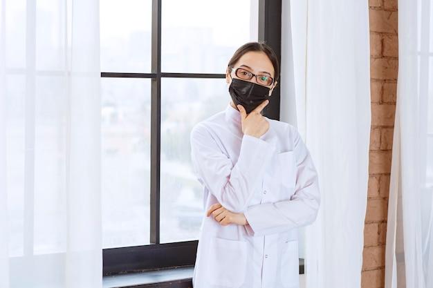 Lekarz w czarnej masce i okularach stoi przy oknie i wygląda na zamyślonego i zdezorientowanego.
