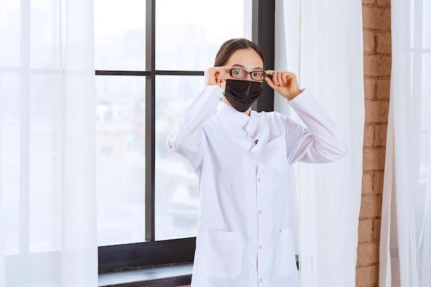 Lekarz w czarnej masce i okularach stojący przy oknie.